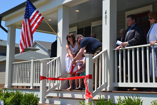 Operation Finally Home Ribbon Cutting Family cutting a giant red ribbon on a home porch with an American Flag