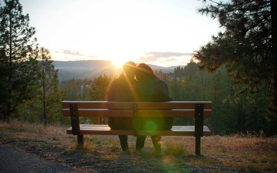 Couple sitting on bench watching sunset over mountains in distance at Eagle Ridge