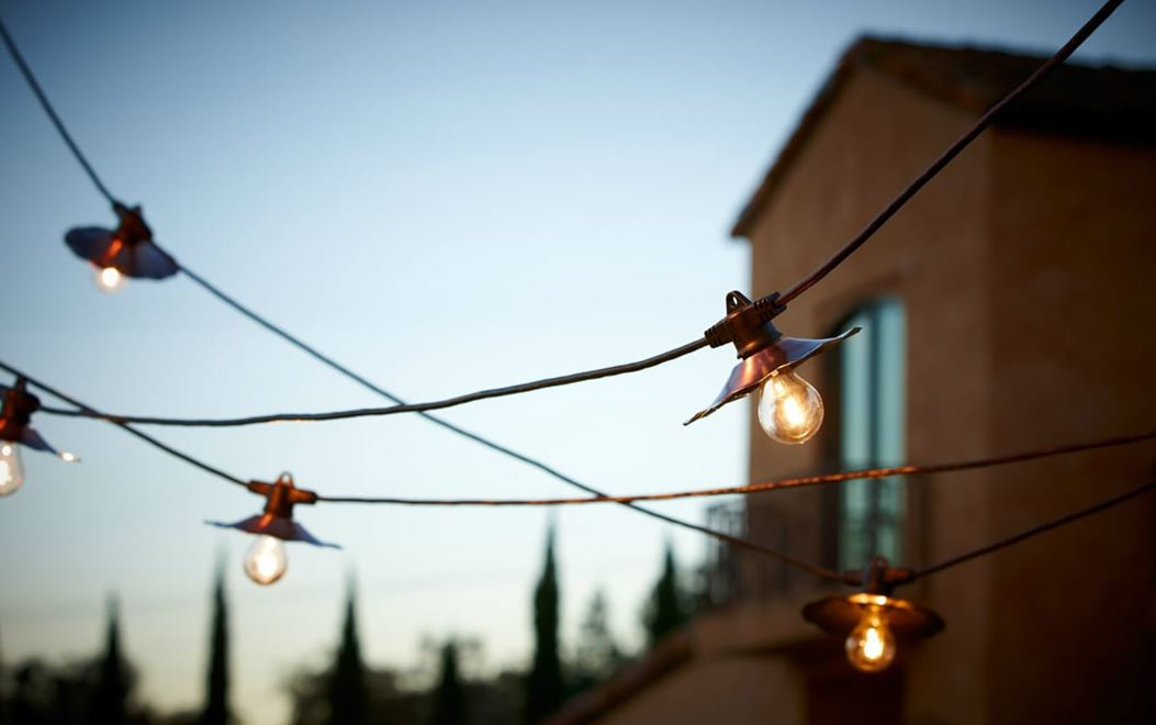 A string of overhead outdoor lights at dusk