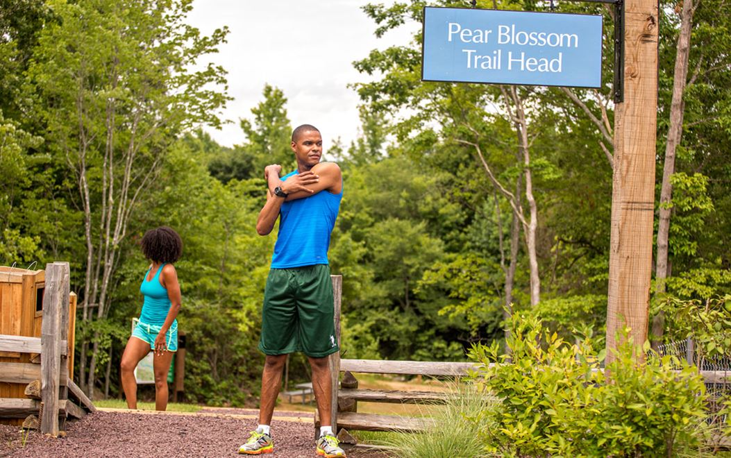 Man stretching at Pear Blossom Trail Head in Embrey Mill community
