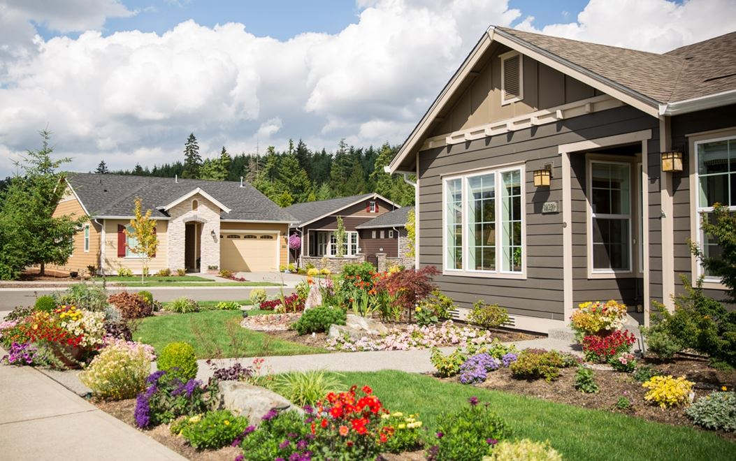 Gray one-story home with flower beds lining the yard and another home in the background