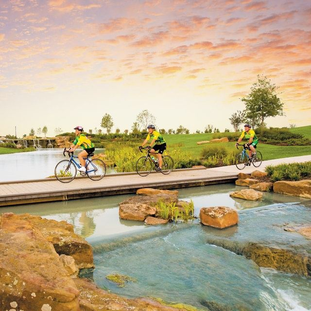 Three people riding bikes on a bridge path over a small river