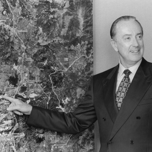 Black & white photo of Bob McLeod pointing to an aerial map
