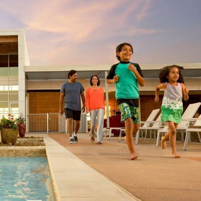 Family of four walking alongside hollyhock community pool