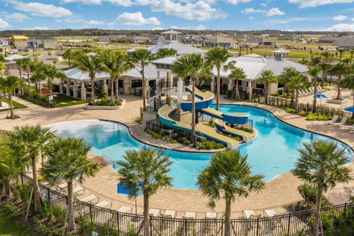 Picture of the Waterset Club community and resident-only clubhouse, fitness center, and resort-style pool in Tampa Bay next to their basketball, pickleball, tennis, and sand volleyball courts.