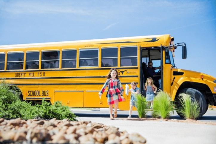 Three girls getting off of a yellow school bus