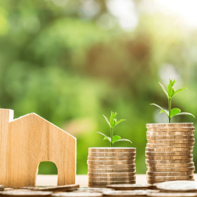 Building Wealth through Homebuying Small Wood House Cutout with stacks of coins increasing in size topped wtih plant sprouts