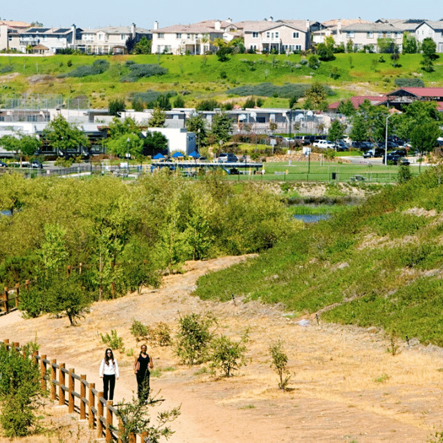 Two women walking on a dirt trail with park, school and neighborhood in the background