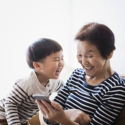 Grandmother Grandchild Laughing Looking at Smart Phone