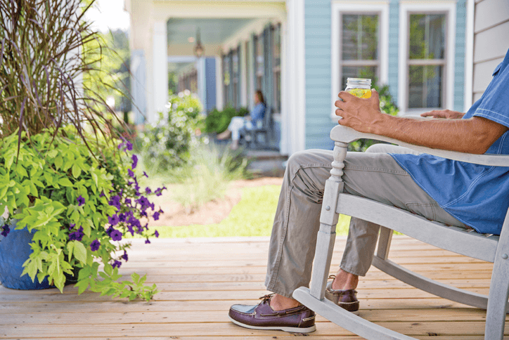 Man in a rocking chair enjoying iced tea on a front porch