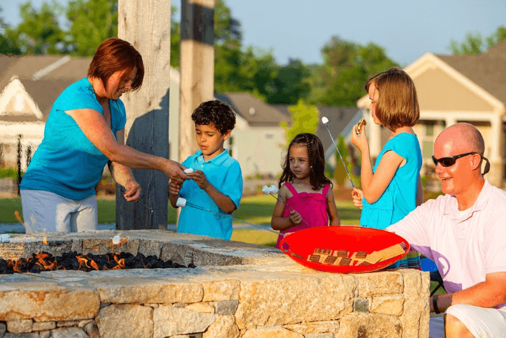 Family of five enjoying s'mores at a firepit