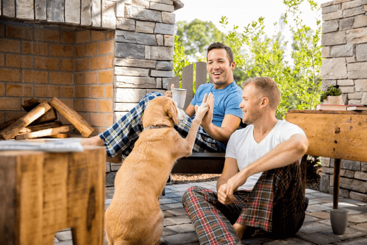 Male couple wearing pajams and high-fiving their dog